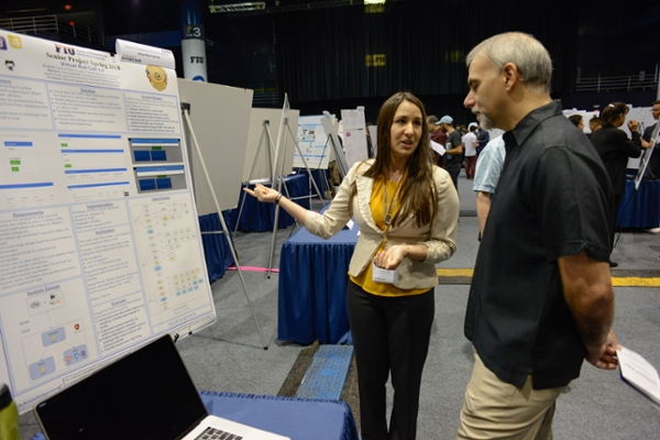 Woman presenting a poster-board to an attendee